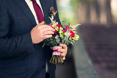 Wedding bouquet in hands of the groom. Wedding rose bouquet in hands of the groom Royalty Free Stock Photos