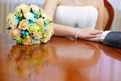 Wedding  bouquet is beside the hands newlywed. Stock Photos