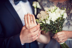 Wedding bouquet and hands with rings Royalty Free Stock Photo