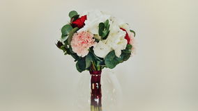 A wedding bouquet of hydrangea, pion-shaped rose, carnation and eucalyptus greens. Bouquet in rotation. stock footage