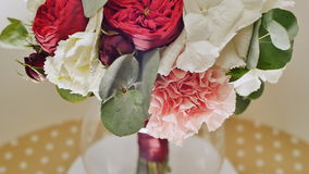 A wedding bouquet of hydrangea, pion-shaped rose, carnation and eucalyptus greens. Bouquet in rotation. stock video footage