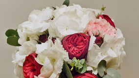 A wedding bouquet of hydrangea, pion-shaped rose, carnation and eucalyptus greens. Bouquet in rotation. stock video