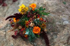 Free Wedding Bouquet In A Bright Autumn Style. On The Background Of Stone Rocks. Marigold Flowers Stock Images - 140038914