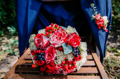 Wedding bouquet with a jacket. Wedding bouquet on a wooden chair with a jacket Royalty Free Stock Image