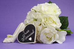 Wedding bouquet with Just Married heart sign against purple background. Royalty Free Stock Photo