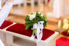 Wedding bouquet laying on bench in church Royalty Free Stock Photography