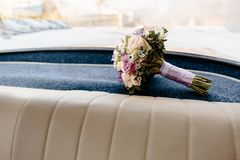 Wedding bouquet laying in an old vintage german car interior stock photography
