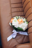 Wedding bouquet on a leather car seat Royalty Free Stock Images