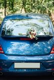 A wedding bouquet lies on a beautiful blue car. wedding decorations royalty free stock images