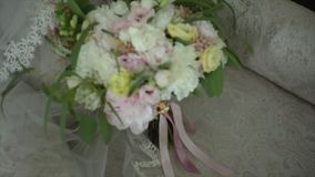 Wedding bouquet lies on a beautiful Chair. The bouquet consists of white and gently pink flowers stock video footage