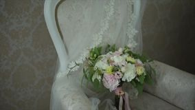 Wedding bouquet lies on a beautiful Chair. The bouquet consists of white and gently pink flowers stock footage
