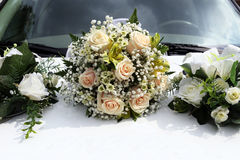 Wedding bouquet lies on the hood of white car stock images