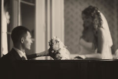 Wedding bouquet lies on the piano while groom plays for a bride.  Royalty Free Stock Image