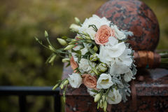 A wedding bouquet lies on a stone fence Royalty Free Stock Photos
