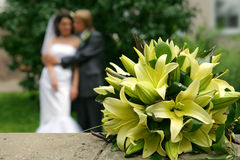 The wedding bouquet of lilies. The bouquet of lilies and blurred newly married couple on background Stock Photos