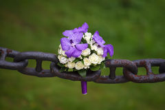 Wedding bouquet lying on an ancient rusty chain Stock Photography