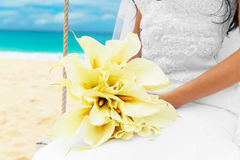 Wedding bouquet lying on the lap of the bride on a tropical beac Stock Image