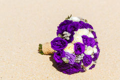 Wedding bouquet lying on the sand on a tropical beach. Royalty Free Stock Photography