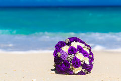 Wedding bouquet lying on the sand on a tropical beach. Blue sea Stock Photos