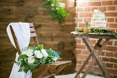 Wedding bouquet lying on wooden chair for wedding ceremony Royalty Free Stock Photography
