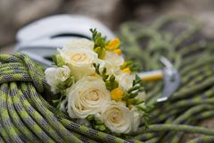 A wedding bouquet made of white roses on a rope with an ice ax Stock Images