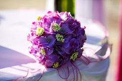 A wedding bouquet mede of violet and yellow flowers lies on a ta Royalty Free Stock Images