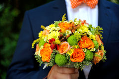 Wedding bouquet in men hands. Groom with orsnge bow holding in hands bouquet Stock Images