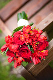 Wedding bouquet of mixed red roses on a bench. Red roses wedding bouquet on bench Stock Image