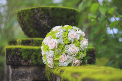 Wedding bouquet on moss covered concrete fence. Stock Photography