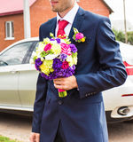 Wedding bouquet with multicolored flowers in the hands of the groom Stock Image