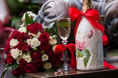 A wedding bouquet near a glass of champagne and a bottle of champagne royalty free stock photography