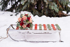 Wedding bouquet on old sled. S in the winter in the snow near spruce Royalty Free Stock Image