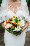 Wedding bouquet. Of orange roses, white and orange chrysanthemums and greenery in the bride`s hands Royalty Free Stock Image