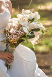 Wedding bouquet of orchids and roses. Beautiful bouquet of orchids in the hands of the bride in a white dress stock photography