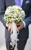 Wedding bouquet of pale pink and yellow flowers and ribbons in hands of groom. Wearing grey suit and violet tie Royalty Free Stock Photo