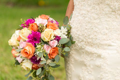 Wedding bouquet and part from a bride. Wedding flowers and colorful wedding bouquet with roses Stock Photography