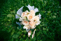 Wedding bouquet from peach-colored roses. On the grass Stock Image