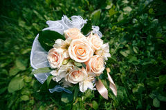 Wedding bouquet from peach-colored roses. On the grass Stock Images