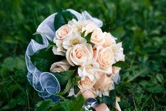 Wedding bouquet from peach-colored roses. On the grass Royalty Free Stock Photos