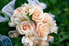 Wedding bouquet from peach-colored roses. On the grass Royalty Free Stock Image