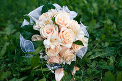 Wedding bouquet from peach-colored roses. On the grass Royalty Free Stock Photo