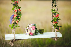 Wedding bouquet of peonies lying on white bench swing decorated with fresh flowers. Royalty Free Stock Photo