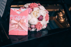 Wedding bouquet with peony. Invitation with Flowers on dark piano Stock Photo