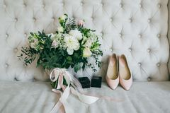 Wedding bouquet, pink bridal shoes and black boxes with rings on a luxury sofa. Indoors. Artwork. White wedding bouquet, pink bridal shoes and black boxes with Stock Photo