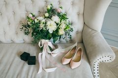 Wedding bouquet, pink bridal shoes and black boxes with rings on a luxury sofa. Indoors. Artwork. White wedding bouquet, pink bridal shoes and black boxes with Royalty Free Stock Photo