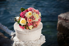 Wedding bouquet of pink and cream roses near blue sea. Royalty Free Stock Image
