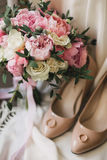 A wedding bouquet of pink peonies, white roses, and eucalyptus, besides beige women`s shoes Royalty Free Stock Photo