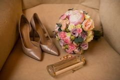 Wedding bouquet with pink peony, yellow roses and greenery with elegant bridal shoes, wedding rings and perfume. details. Wedding bouquet with pink peony, yellow Stock Photography