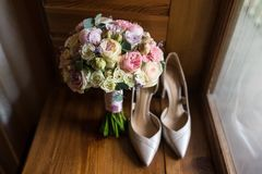 Wedding bouquet with pink peony, yellow roses and greenery with elegant bridal shoes. Wedding Royalty Free Stock Photography