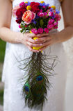 Wedding bouquet of pink, red, blue and yellow flowers and hand of bride Stock Photos